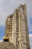 Crane in front of a stripped down, half demolished apartment building. Crane in front of an old stripped down, half demolished  apartment building, in Rabot Stock Photography
