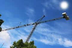 Crane gli edifici costruiti sole ed alloggiato il metallo della struttura di industria dell'edilizia Immagini Stock