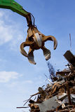 A crane grabber loading a metal. A crane grabber and a rusty metal  heap Stock Photos