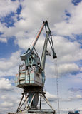 Crane in harbor. Blue crane in the river harbor with dynamic clouds and blue sky in background Royalty Free Stock Photo