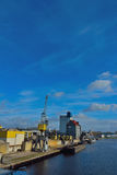 Crane and harbor. Cargo crane, ships docked in the harbor of EIndhoven, Netherlands Royalty Free Stock Image