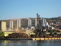 Crane in harbor. Huge, industrial crane unloading old waste of steel in harbor in city Rijeka Stock Photography