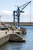 Crane in the harbor. People near a crane in the harbor of Puerto de la Cruz in Tenerife. It is an editorial image vertically on a sunny day taken in May 2016 Royalty Free Stock Photography