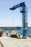 Crane in the harbor. People near a crane in the harbor of Puerto de la Cruz in Tenerife. It is an editorial image vertically on a sunny day taken in May 2016 Royalty Free Stock Images