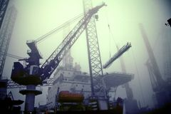 Crane in a harbor. Crane working at the harbor of IJmuiden in the Netherlands on a foggy day Royalty Free Stock Photos