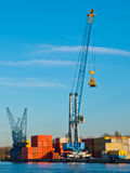 Crane in a harbour. Crane with stacked containers in a harbour Royalty Free Stock Image
