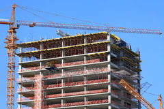 Crane and high-rise building under construction against blue sky. Crane and high-rise building under construction against blue sky stock photo