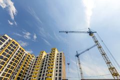 Crane and high rise building under construction against blue sky. Modern architecture background Royalty Free Stock Images