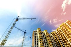 Crane and high rise building under construction against blue sky. Modern architecture background Royalty Free Stock Photos