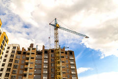 Crane and high rise building under construction against blue sky. Modern architecture background Stock Images