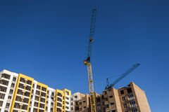 Crane and high rise building under construction against blue sky. Modern architecture background royalty free stock photo