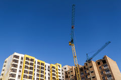 Crane and high rise building under construction against blue sky. Modern architecture background stock photo