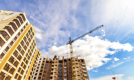 Crane and high rise building under construction against blue sky. Modern architecture background Stock Photos