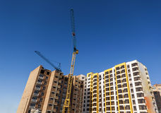 Crane and high rise building under construction against blue sky. Modern architecture background Royalty Free Stock Photography