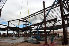 Crane Hoisting a Truss-Joist. A crane hoists a large truss-joist into position while ropes attached to each end allow iron workers to guide the joist as it rises Royalty Free Stock Image