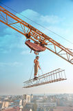 Crane holding construction with man over city. Stock Photos