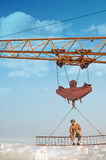 Crane holding iron construction, where sitting builder. Stock Photography