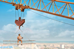 Crane holding iron construction, where sitting builder. Royalty Free Stock Images