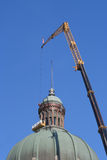 A Crane holding a lift to clean the dome of the building Royalty Free Stock Images