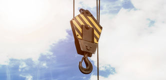 Crane hook with a cloudy sky wide version. A crane hook with a cloudy sky wide version Royalty Free Stock Image