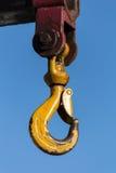 Crane Hook giallo su un fondo blu fotografie stock libere da diritti