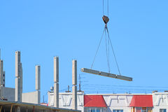 Crane hook with load and part of building under construction Royalty Free Stock Images
