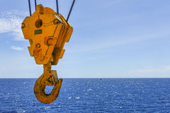 Crane hook in the sea with sky and clouds background on offshore Stock Photography