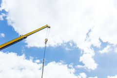 Crane hook with straps is hanging above building site Stock Photos