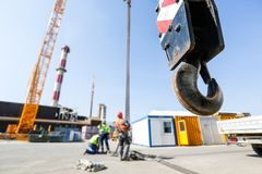 Crane hook with workers in the background Royalty Free Stock Images
