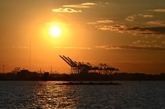 Crane on the Horizon. The silhouette of the cranes of New York Port against the sunset Royalty Free Stock Image