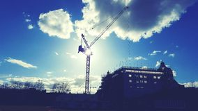 Crane and hotel on blue sky Royalty Free Stock Photo