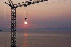 Crane il sole di cattura del gancio durante il tramonto sopra il mare Fotografia Stock Libera da Diritti