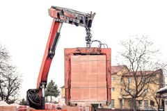 Crane or industrial forklift delivers a brick pallet at building construction site, isolated on white sky Royalty Free Stock Photography
