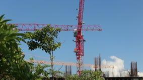 Crane jib finishes turn above frame of skyscraper stock video