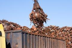Crane l'arraffone che carica un camion con lo scarto di metallo Immagini Stock
