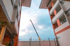 Crane la costruzione di mattoni della costruzione nel fondo del cielo blu e della città Fotografia Stock Libera da Diritti