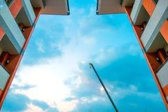 Crane la costruzione di mattoni della costruzione nel fondo del cielo blu e della città Fotografie Stock