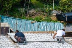 Crane la parte di sollevamento di un pavimento del cemento con la regolazione dei lavoratori Immagine Stock