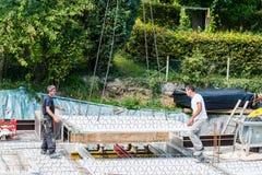 Crane la parte di sollevamento di un pavimento del cemento con la regolazione dei lavoratori Fotografie Stock
