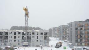 Crane la pieza de la casa de bloque de cemento de la elevación y los trabajadores trabajan en invierno almacen de video