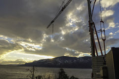 Crane on the lake. Work, development, industry is encompassing in Okanagan Valley cranes construction Lakes Stock Photo