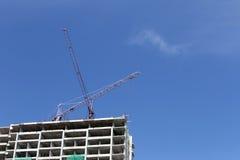 Crane lavorare ad una costruzione in costruzione nel tempo del giorno Fotografie Stock Libere da Diritti