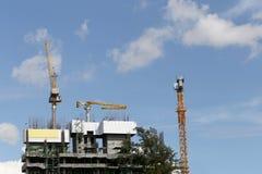 Crane lavorare ad una costruzione in costruzione nel tempo del giorno Fotografie Stock