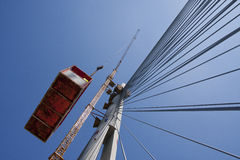 Crane lift on suspended bridge. Against the blue sky Royalty Free Stock Photo