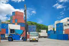 Crane lifter handling container box loading to truck. Stock Image