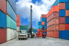 Crane lifter loading container box into truck in import export l Stock Photography