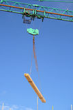 Crane lifting. Close up of a crane lifting planks of wood on a construction site Royalty Free Stock Photo