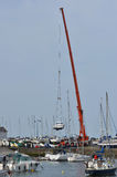 Crane lifting boat at harbourside. Stock Image