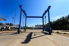 Crane lifting boats at harbor Royalty Free Stock Photos