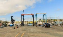 Crane lifting boats at harbor Royalty Free Stock Photo